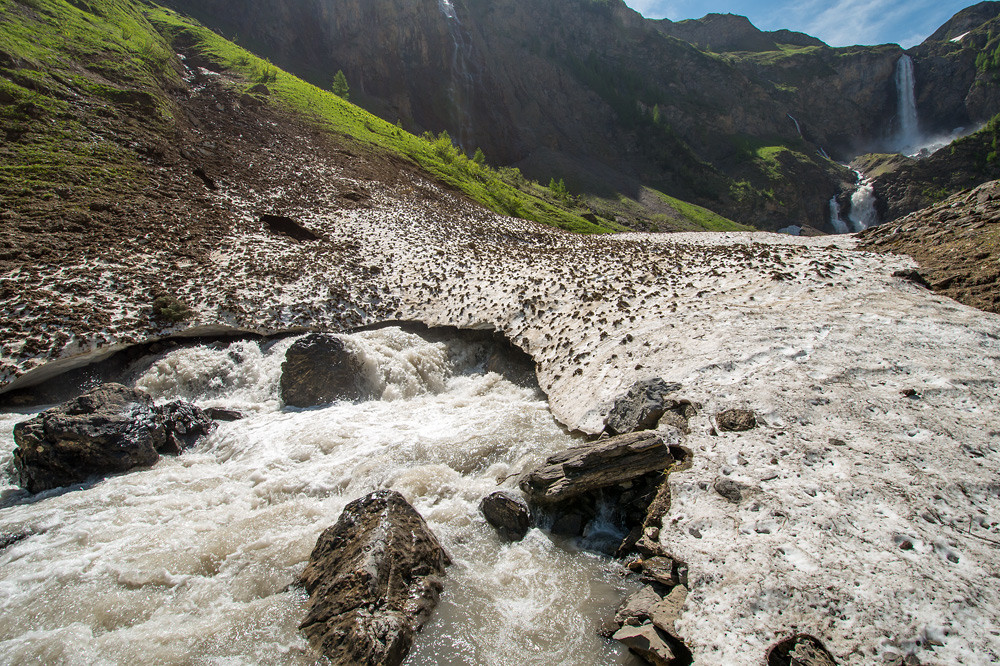 Ein Bach sucht sich seinen Weg unter einem alten Lawinenkegel hindurch: Geltental (1600 m), Berner Oberland, 17.06.2013