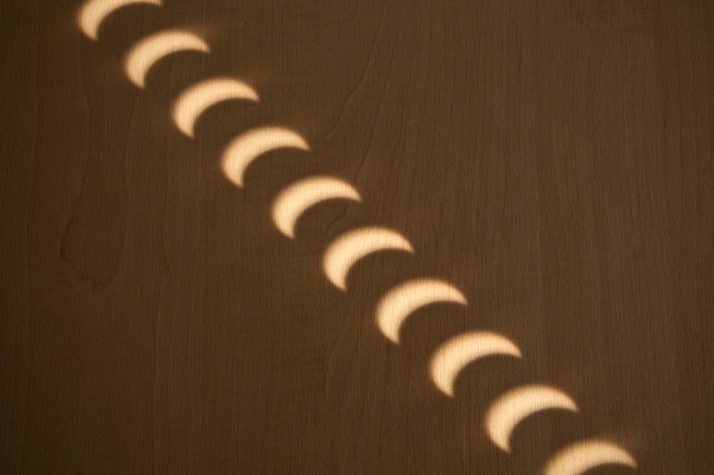 Wer keine SoFi-Brille oder eine Spezialfolie besitzt, kann sich mit dem Lochkamera-Prinzip behelfen. Dieses Muster wurde während der partiellen Sonnenfinsternis am 04.01.2011 durch die Löcher von Jalousien auf eine Holzwand projiziert