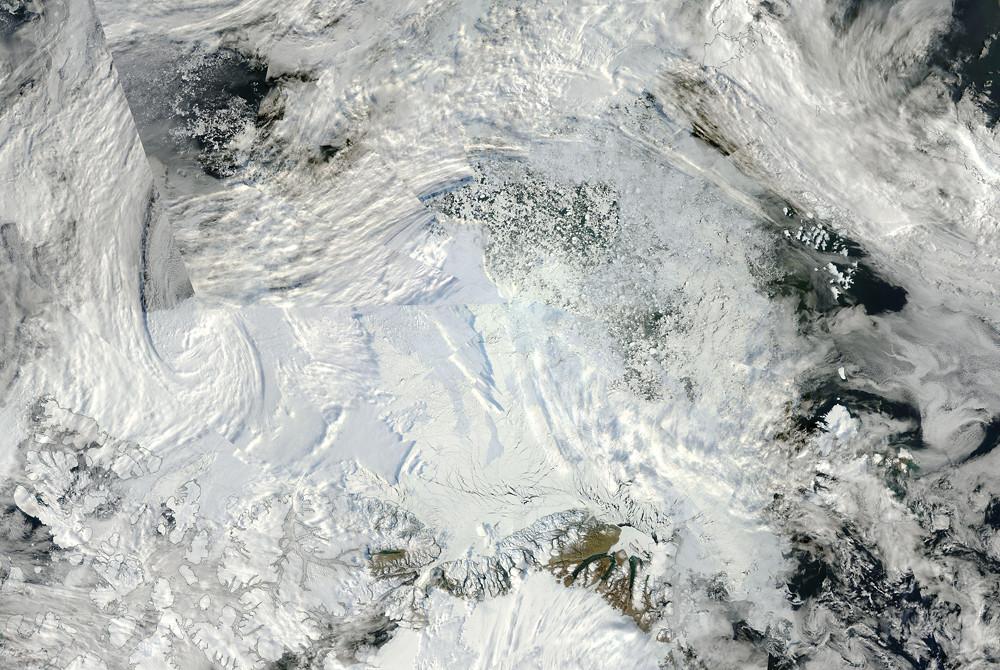 Satellitenaufnahme der Nordpolregion vom 08.09.2016. Der Norpol befindet sich in der Bildmitte, wo die Einzelbilder sternförmig zusammenfliessen. Am unteren Bildrand ist Grönland zu sehen. Interaktive Bildquelle